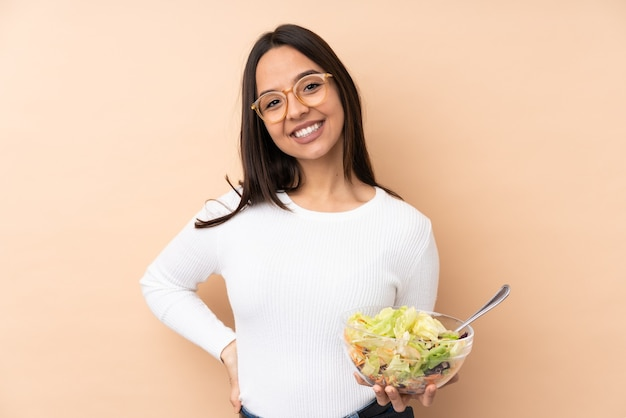 Jong donkerbruin meisje dat een geïsoleerde salade houdt