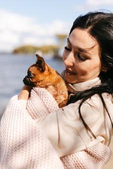 Jong donkerbruin meisje dat een kleine bruine hond dicht omhoog houdt