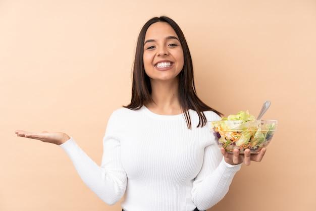 Jong donkerbruin meisje dat een salade over geïsoleerde muur met geschokte gelaatsuitdrukking houdt