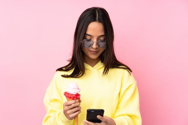 Jong donkerbruin meisje die een cornetroomijs over geïsoleerde roze muur houden die een bericht met mobiel verzenden