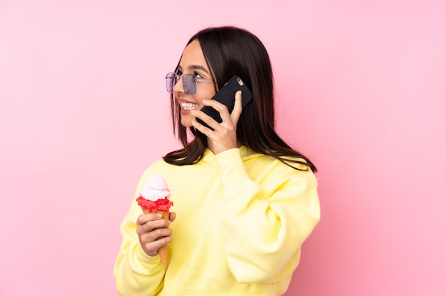 Jong donkerbruin meisje die een cornetroomijs over roze te houden holdingskoffie en mobiel houden