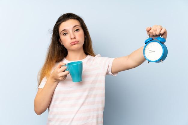 Jong donkerbruin meisje die een kop van koffie en uitstekende klok over geïsoleerde muur houden
