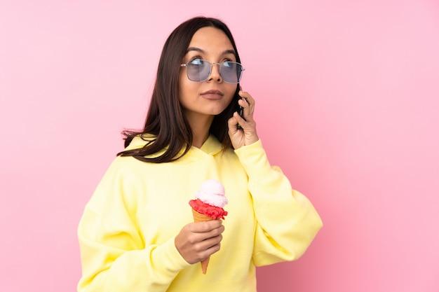 Jong donkerbruin meisje die een kornetroomijs over de geïsoleerde roze weg te nemen koffie van de muurholding en mobiel houden