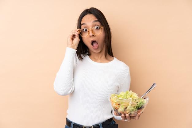 Jong donkerbruin meisje die een salade over geïsoleerde muur met glazen houden en verrast