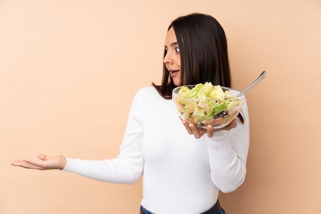 Jong donkerbruin meisje die een salade over geïsoleerde muur met verrassingsgelaatsuitdrukking houden