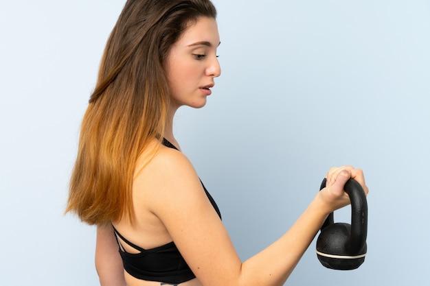 Jong donkerbruin meisje die gewichtheffen met kettlebell maken