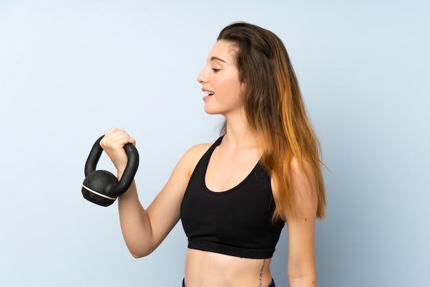 Jong donkerbruin meisje die gewichtheffen met kettlebell over geïsoleerde muur maken