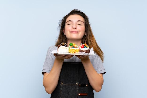 Jong donkerbruin meisje die minicakes houden die van de geur van hen genieten