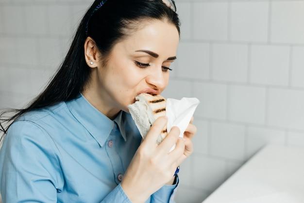 Jong donkerbruin meisje in blauw overhemd dat een broodje eet in café