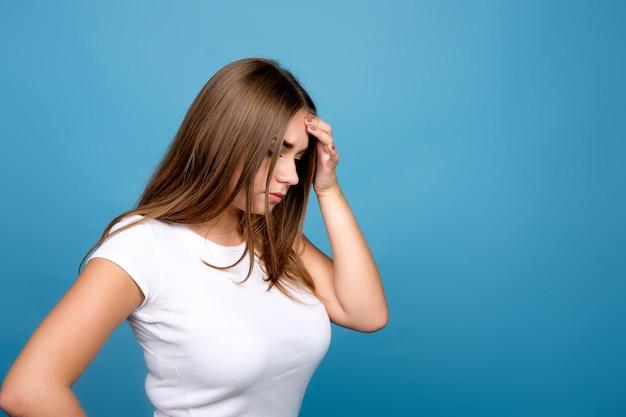 Jong donkerbruin meisje in witte t-shirt die iets, vergeetachtigheidsuitdrukking, blauwe achtergrond proberen te herinneren