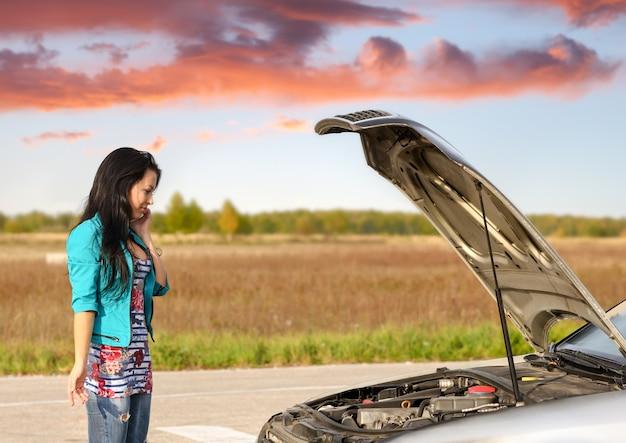 Jong donkerbruin meisje met afgebroken auto met open kap oproep om hulp