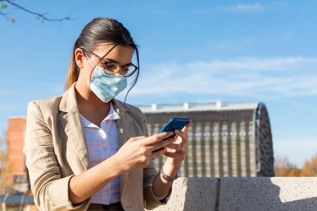 Jong donkerbruin meisje met een gezichtsmasker dat aan een parkbank buiten haar bureau werkt. praten op haar mobiele telefoon. bedrijfsconcept, technologie en telewerken. coronapandemie.