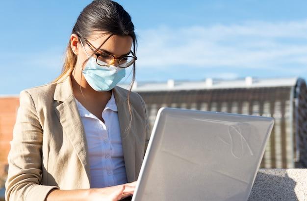 Jong donkerbruin meisje met een gezichtsmasker dat aan een parkbank buiten haar bureau werkt. werken met haar laptop. bedrijfsconcept, technologie en telewerken. coronapandemie.