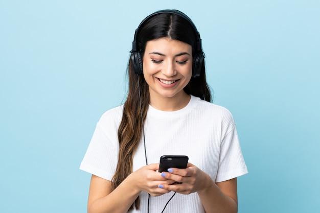 Jong donkerbruin meisje over blauwe muur het luisteren muziek en het kijken aan mobiel