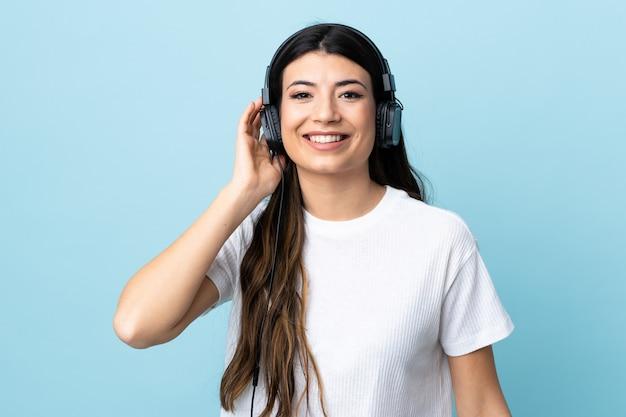 Jong donkerbruin meisje over blauwe muur het luisteren muziek