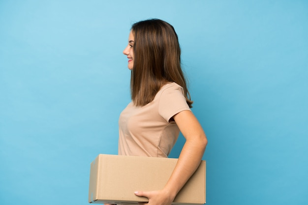 Jong donkerbruin meisje over geïsoleerd blauw dat een doos houdt om het naar een andere plaats in zijpositie te verplaatsen