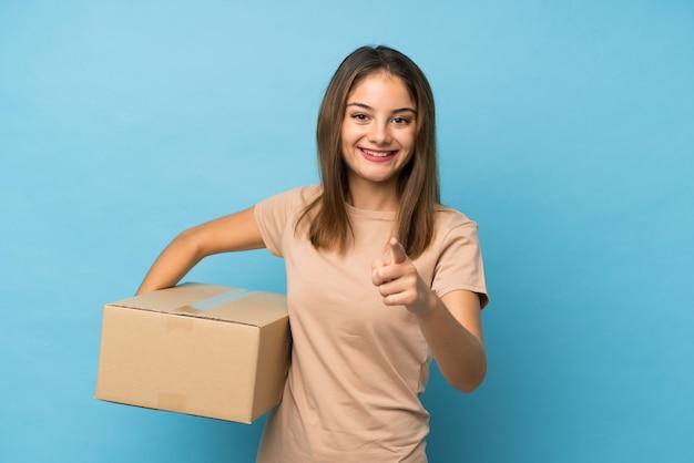 Jong donkerbruin meisje over geïsoleerd blauw dat een doos houdt om het naar een andere plaats te verplaatsen terwijl het richten naar de voorzijde