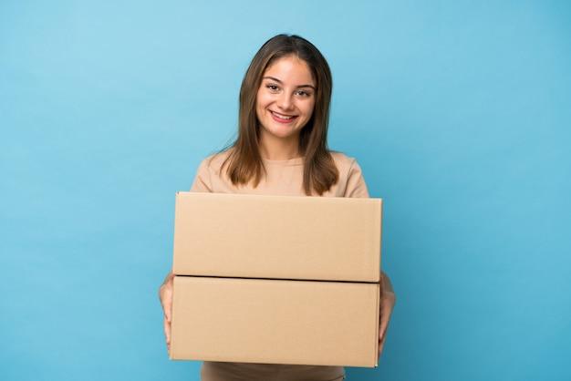 Jong donkerbruin meisje over geïsoleerd blauw dat een doos houdt om het naar een andere plaats te verplaatsen