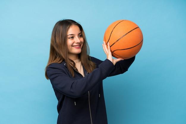 Jong donkerbruin meisje over geïsoleerde blauwe muur met bal van basketbal