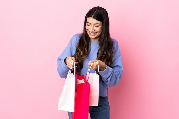 Jong donkerbruin meisje over geïsoleerde roze holdings het winkelen zakken en het kijken binnen het