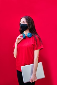 Jong donkerbruin studentenmeisje met gezichtsmasker dat laptop en hoofdtelefoons op rode achtergrond houdt