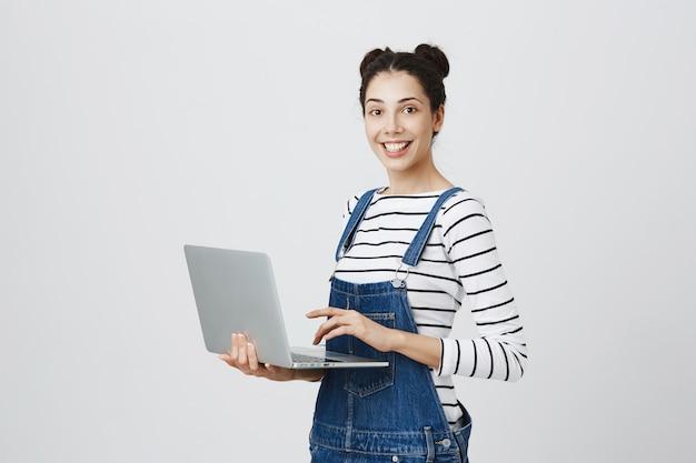 Jong duizendjarig meisje met behulp van laptop, vrouwelijke student essay schrijven op de computer