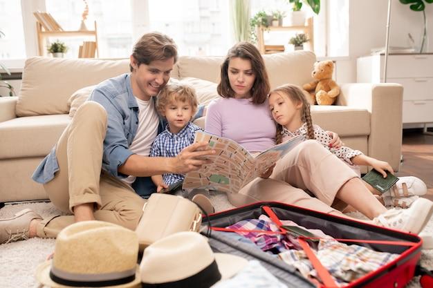 Jong eigentijds gezin van twee kleine kinderen en hun ouders die naar de kaart kijken terwijl ze zich voorbereiden op een reis naar een ander land