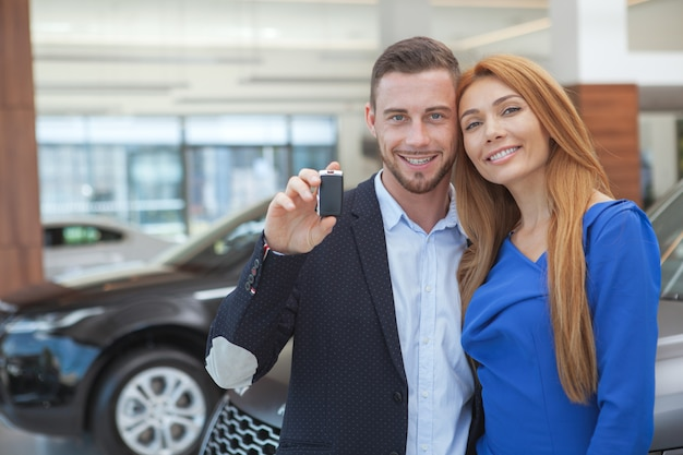 Jong elegant paar die luxueuze auto kopen bij het handel drijven