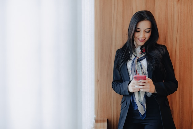 Jong emotioneel aantrekkelijk meisje in bedrijfsstijlkleren bij een venster met een telefoon in een modern kantoor of auditorium