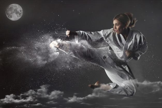 Jong emotioneel karatemeisje probeert de maan te raken