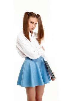 Jong emotioneel meisje in het eenvormige stellen, geïsoleerd op witte muur
