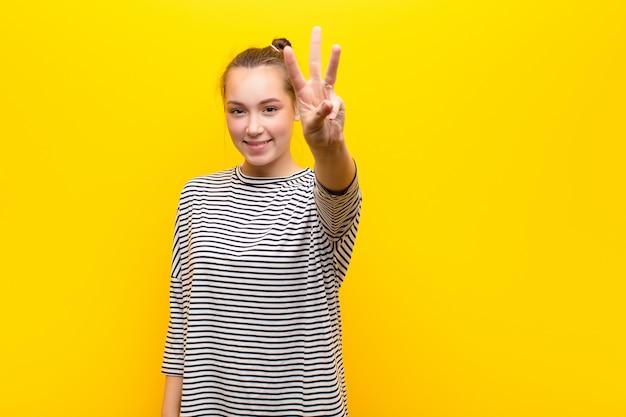 Jong en blond mooi meisje die vriendschappelijk glimlachen kijken, tonend nummer twee of seconde met voorwaartse hand, aftellend tegen gele muur