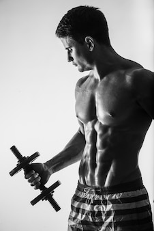 Jong en fit mannelijk model poseren zijn spieren oppompen met halters in een sportschool op zoek naar links geïsoleerd