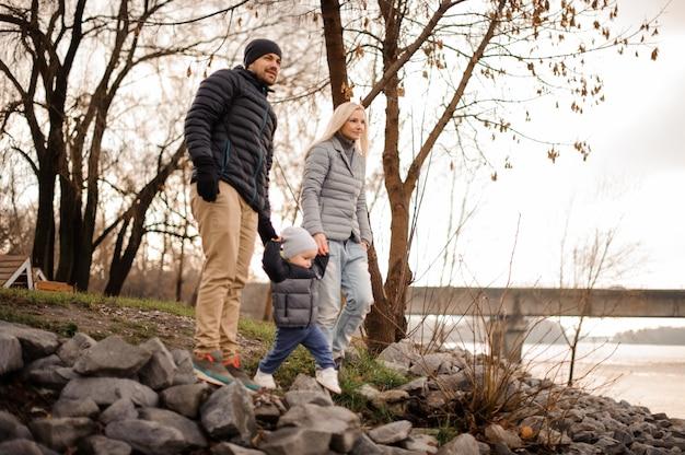 Jong en gelukkig familiepaar dat met de zoon loopt