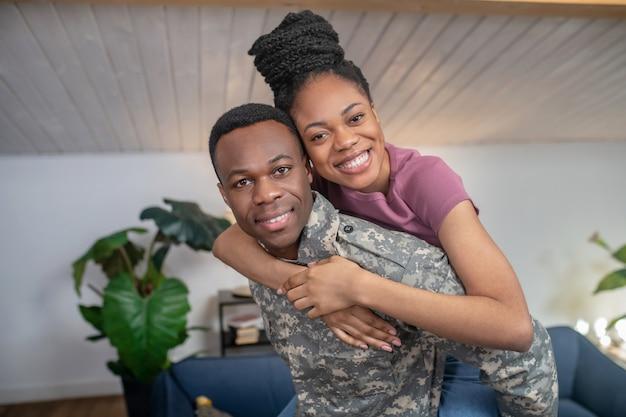 Jong en gelukkig. fijne jonge militair met een donkere huid die zijn mooie vrouw op zijn rug vasthoudt met een hoog kapsel dat thuis in de kamer staat