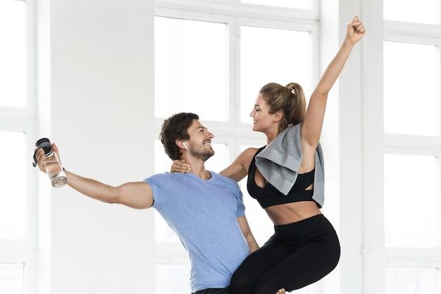 Jong en gelukkig fitnesspaar tijdens gymnastiektraining in de sportschool