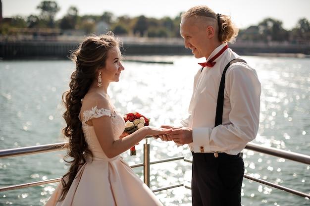 Jong en gelukkig getrouwd stel dat de trouwringen op de achtergrond van de zee ruilt
