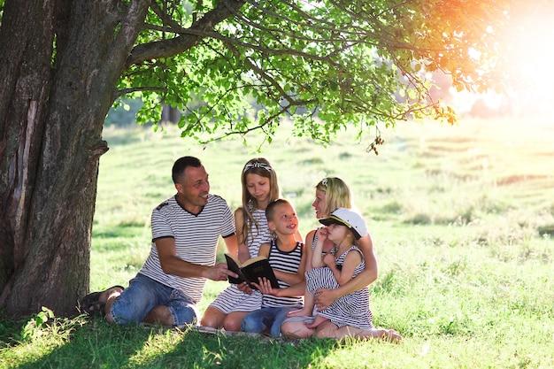 Jong en gelukkig gezin dat de bijbel leest in de natuur
