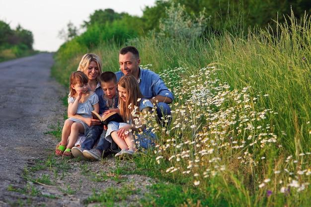 Jong en gelukkig gezin met kinderen die de bijbel lezen in de natuur