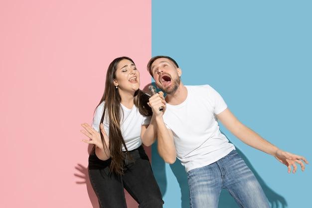 Jong en gelukkig man en vrouw in vrijetijdskleding op roze, blauwe tweekleurige muur, zingen
