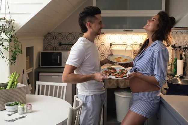 Jong en gelukkig paar dat op een baby wacht. echtgenoot en zijn zwangere vrouw in de keuken tijdens het ontbijt.