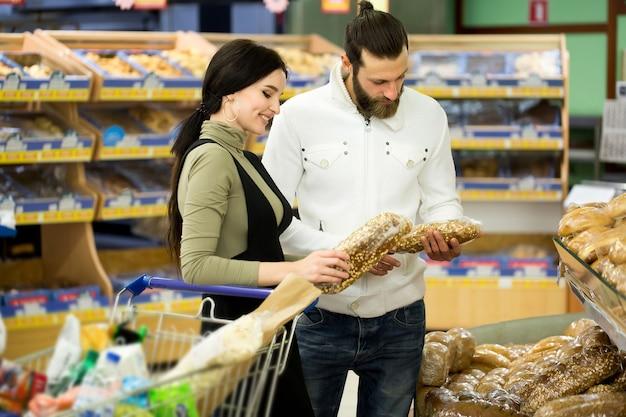 Jong en gelukkig paar dat vers gebak kiest, dat zich samen in de bakkerijafdeling van de supermarkt bevindt