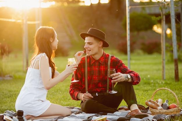 Jong en gelukkig paar die van een picknick genieten die op parkside in de zomerdag wordt uitgespreid