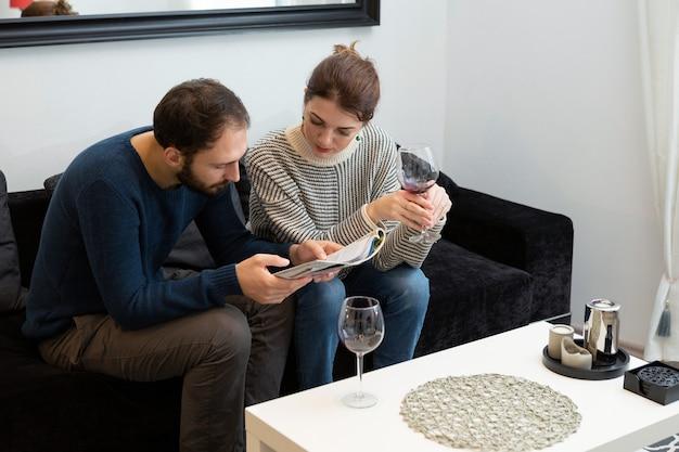 Jong en gelukkig stel dat wijn drinkt en thuis ontspant