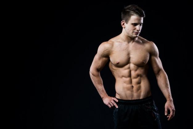 Jong en geschikt mannelijk model die zijn spieren stellen die naar beneden geïsoleerd op zwarte muur kijken