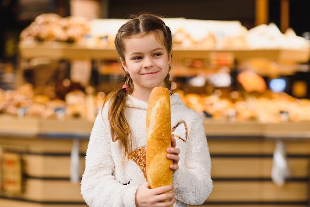 Jong en grappig meisje stokbrood eten voor de bakkerij-winkel