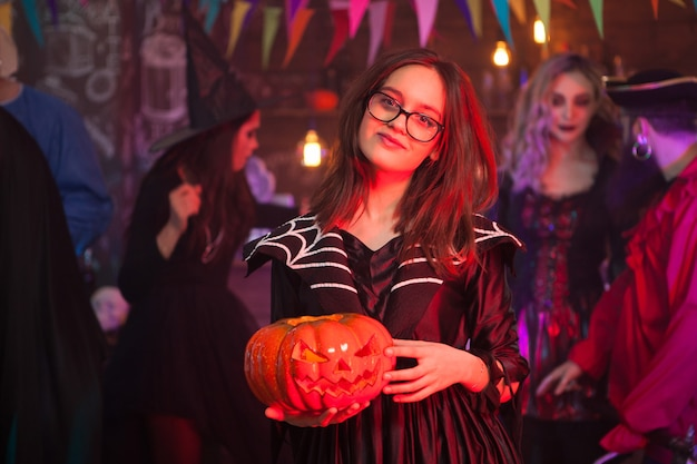 Jong en griezelig meisje verkleed als een heks die een pompoen vasthoudt tijdens halloween-feest. vrienden verzamelen voor halloween.