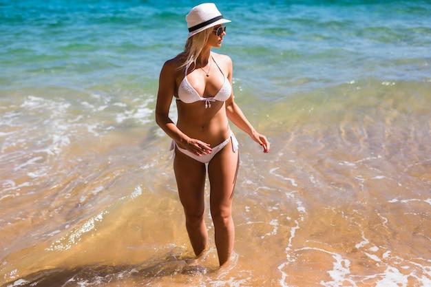 Jong en mooi meisje hebben een seizoensgebonden wintervakantie op het strand in een exotisch land