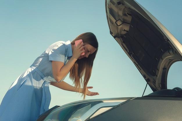 Jong en mooi meisje in de buurt van een kapotte auto met een open kap. problemen met de auto, start niet, werkt niet.