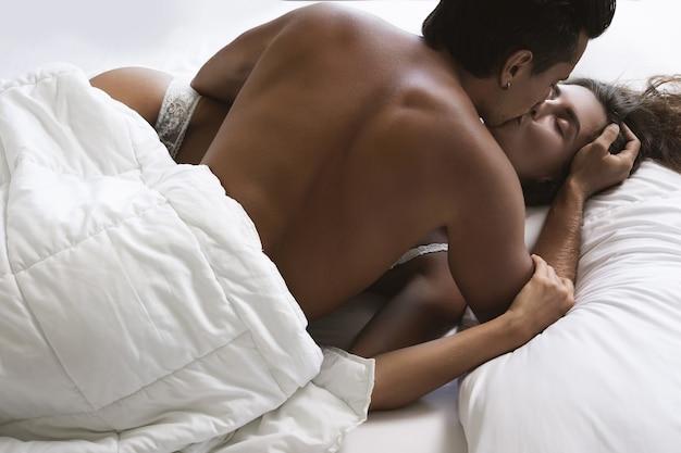 Jong en mooi paar in omhelzing liggend op het bed